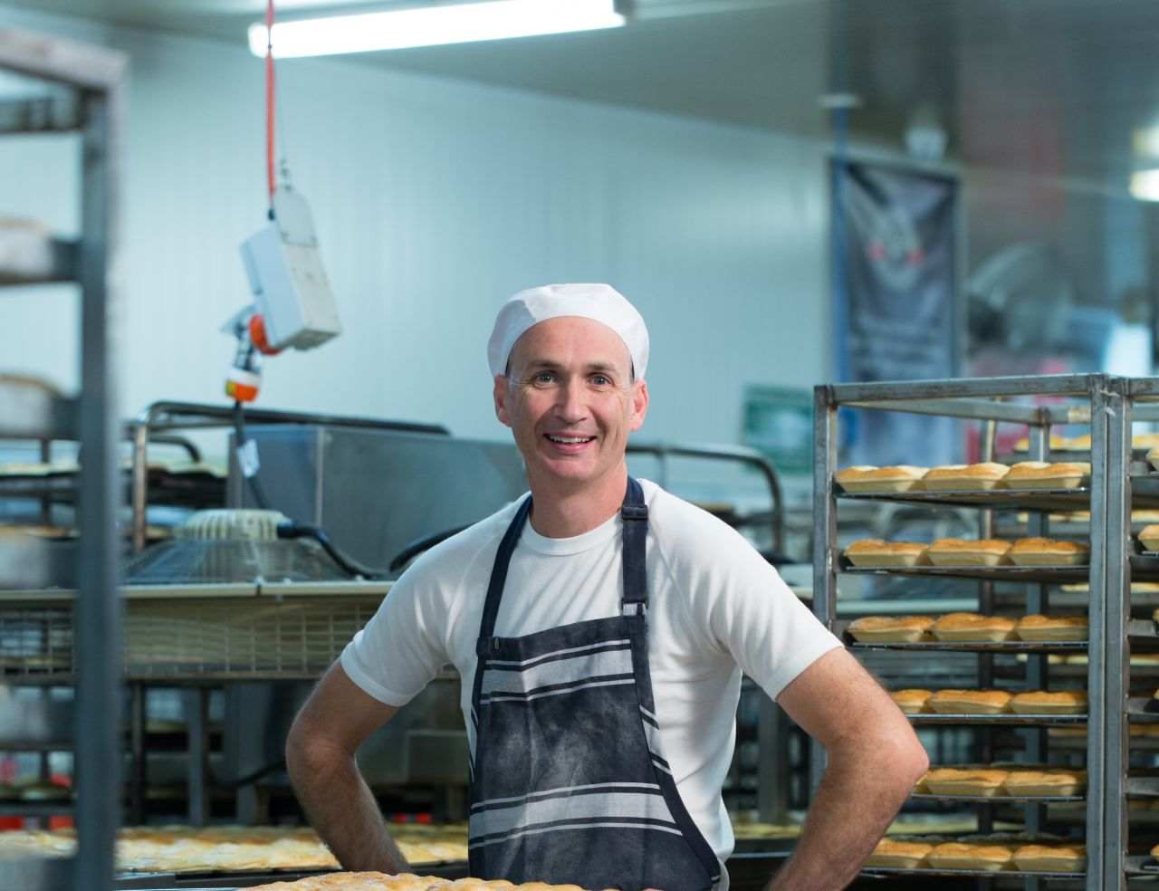 A baker standing in the bakery with a tray of pies